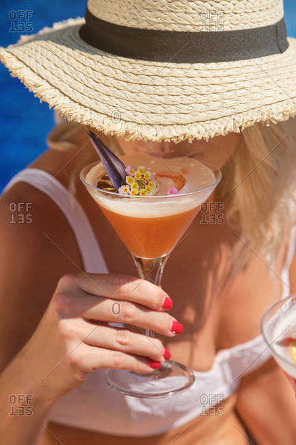 From above of crop anonymous female traveler in straw hat and white bikini enjoying exotic fruit cocktail decorated with flowers while relaxing on poolside during summer holidays