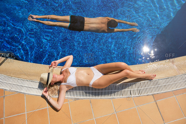 From above of unrecognizable young slim female in bikini covering face with straw hat while lying on poolside and sunbathing during summer vacation