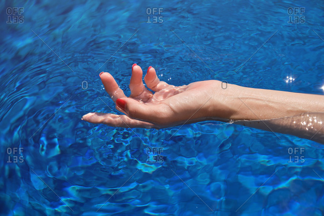 High angle of crop anonymous female traveler with red nails swimming in blue water of pool on sunny day