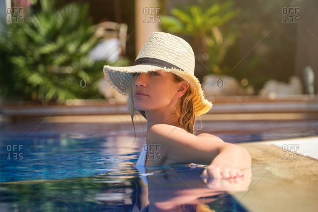 Side view of attractive relaxed young female in straw hat chilling in outdoor swimming pool and enjoying summer holidays in tropical resort