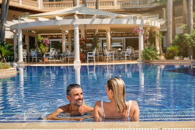Cheerful adult bearded man chatting with girlfriend while relaxing together in outdoor swimming pool during romantic summer holidays in tropical resort