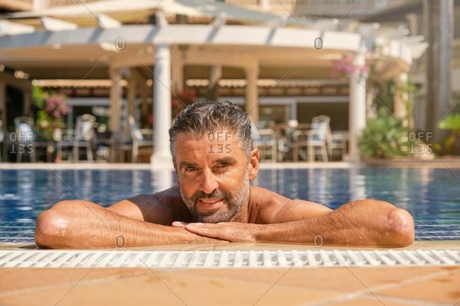 Portrait of happy adult bearded ethnic male tourist relaxing in water of swimming pool and looking at camera in sunny summer day while spending holidays in tropical resort