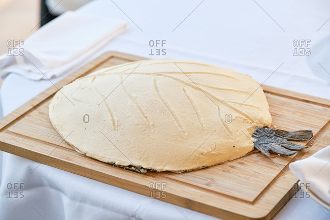 Whole fish baked in salt dough crust served on wooden board in modern restaurant