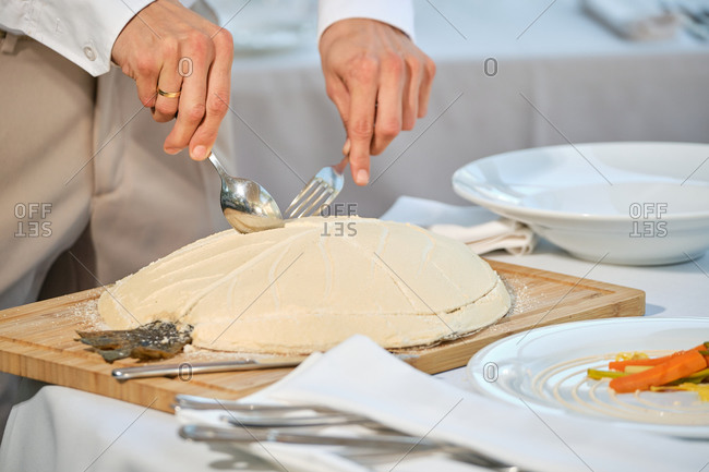 Crop anonymous waiter cutting crust of fish baked in salt dough while serving food to clients in modern restaurant