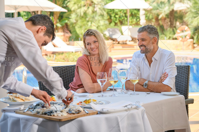 Elegant multiethnic couple enjoying delicious dishes and drinks served by professional waiter during lunch on restaurant terrace against poolside in tropical resort