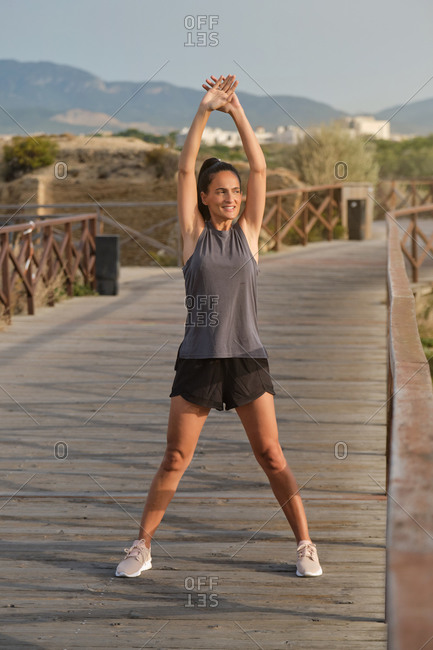 Happy cheerful sporty female smiling and performing exercises raising hands and looking away