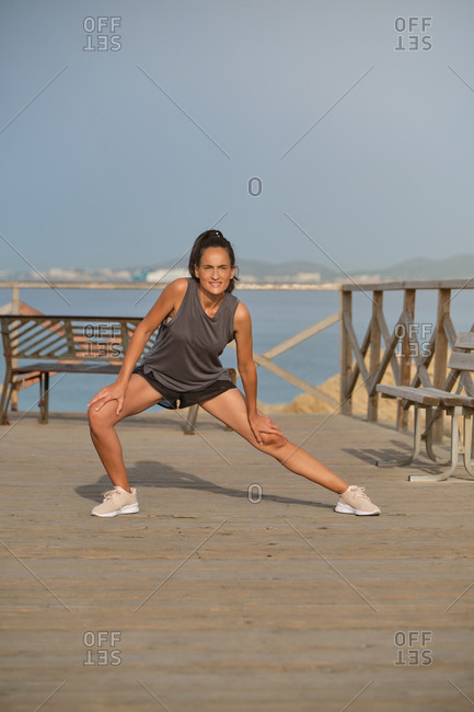 Full body of young slim female exercising on wooden pier near water on misty day