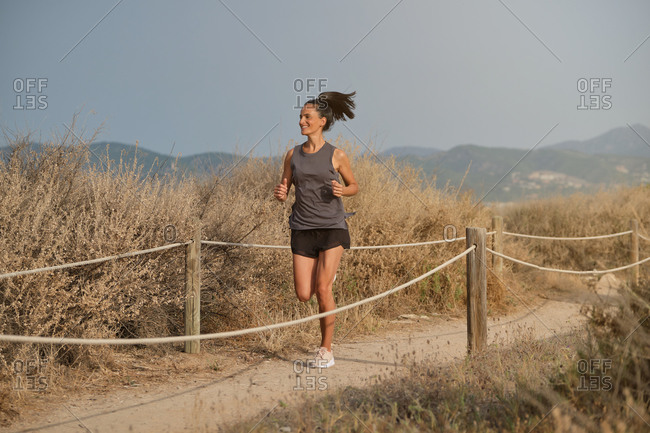 Full body of tanned female running in dry field and enjoying sport near foggy mountains