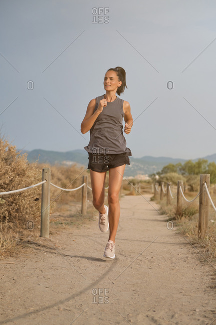 Young sporty athletic female in activewear running fast on path at countryside