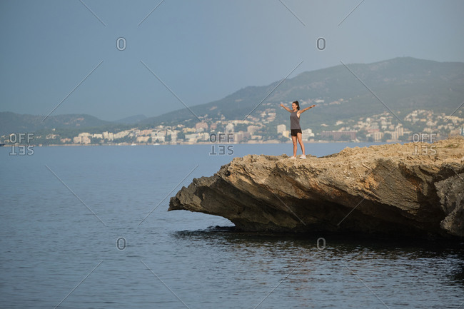 Young female on seashore in picturesque landscape of town in misty green mountains