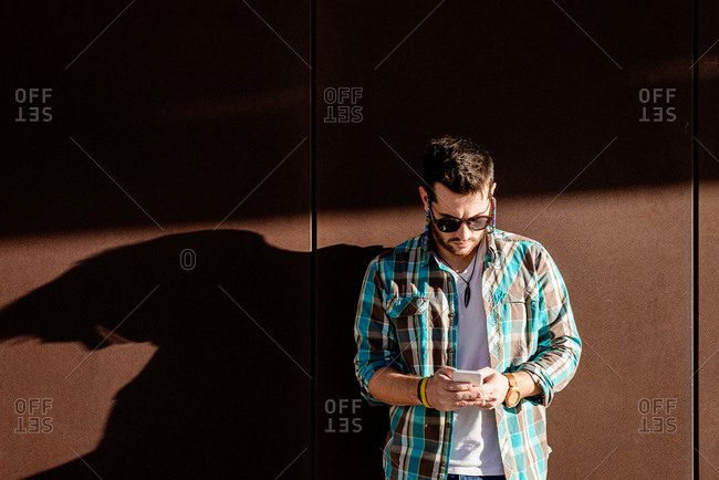 Focused young male in stylish outfit using contemporary mobile phone against modern building wall on sunny weather
