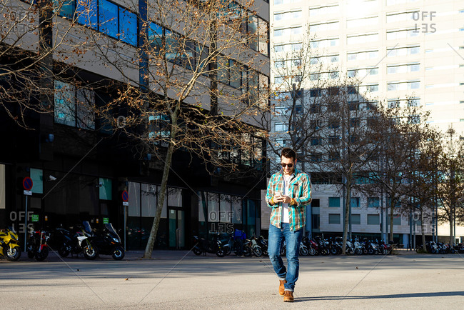 Young male walking in stylish outfit using contemporary mobile phone against modern building wall on sunny weather while talking on the phone