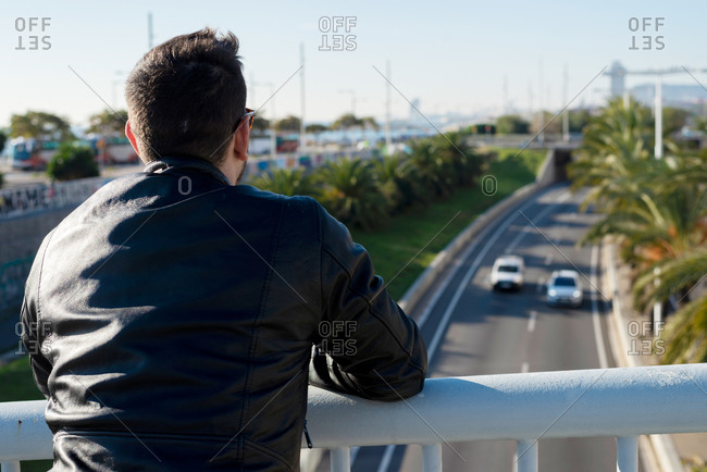 Back view unrecognizable male in black leather jacket leaning on railing above city road on sunny day