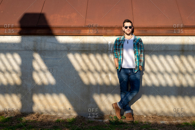Handsome young male in stylish outfit standing with hands in pocket against shabby building wall on sunny weather