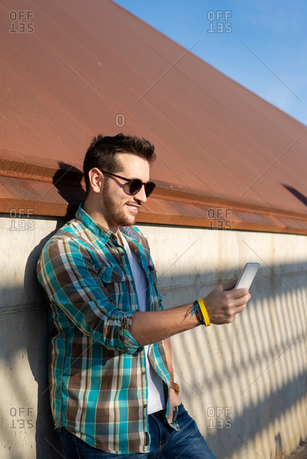 Positive young male in checkered shirt and sunglasses taking selfie on modern mobile phone while standing near shabby concrete wall on street