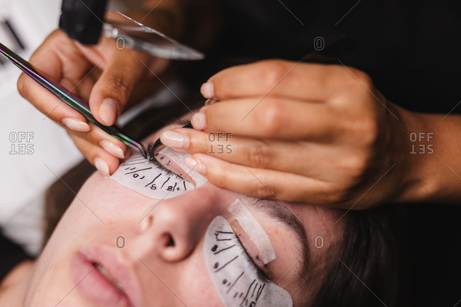 From above of crop anonymous master doing eyelash extension after mapping for unrecognizable female customer in face mask
