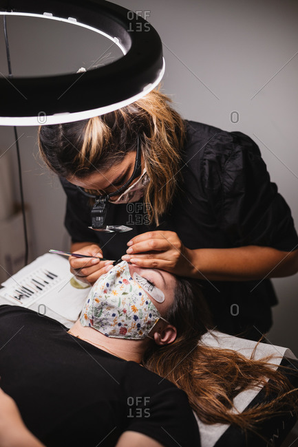 Female master doing eyelash extension after mapping for unrecognizable female customer in face mask
