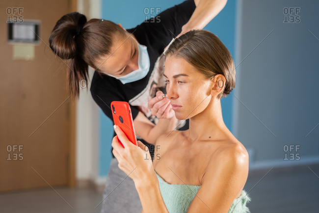 Concentrated female makeup artist applying cosmetic product on face of model sitting in salon and using smartphone