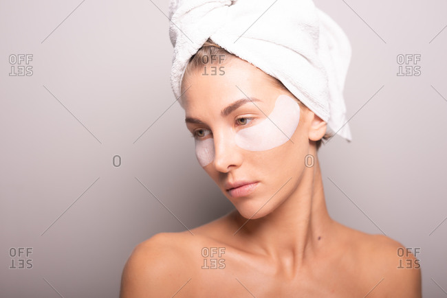 Charming female model with towel turban on head and hydrating eye patches on face standing on violet background in studio and looking away