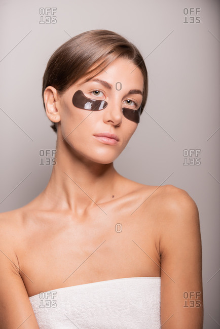 Charming female with perfect skin standing with black eye patches in studio looking at camera