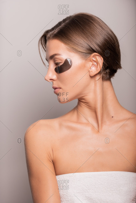Charming female with perfect skin standing with black eye patches in studio looking away