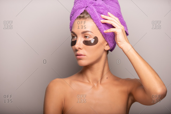 Charming female with perfect skin standing with towel turban and eye patches in studio on violet background and looking away