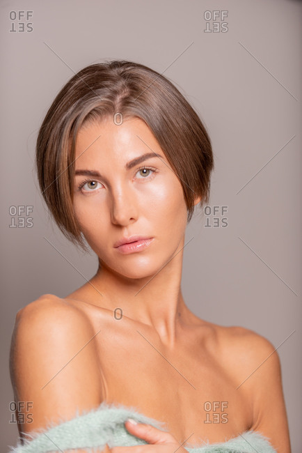 Charming female model with short hair and bare shoulders standing on violet background in studio and looking at camera