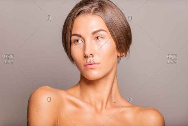 Charming female model with short hair and bare shoulders standing on violet background in studio and looking away