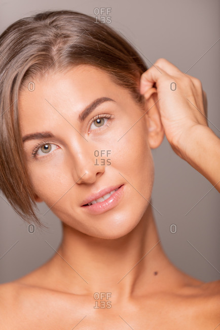 Charming female model with short hair and bare shoulders standing on violet background in studio and smiling at camera