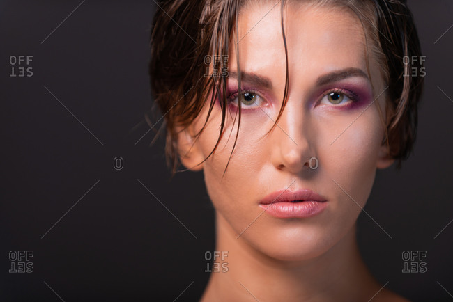 Charming female model with wet short hair and bare shoulders standing on violet background in studio and looking at camera
