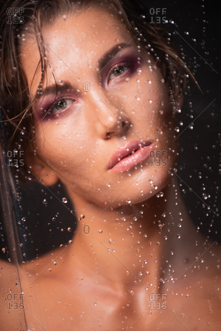 Attractive young sensual female with bare shoulders and perfect makeup standing behind transparent glass with water drops looking at camera