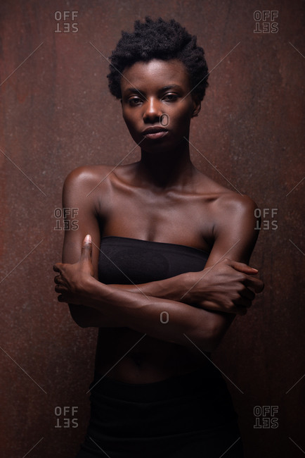 Sensual African American female wearing tight black top with bare shoulders standing with arms crossed in dark studio and looking at camera provocatively