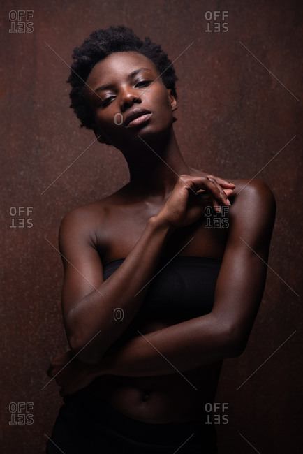 Seductive African American female model wearing black top with bare shoulders holding raised arm in front and looking at camera during photo session in dark studio