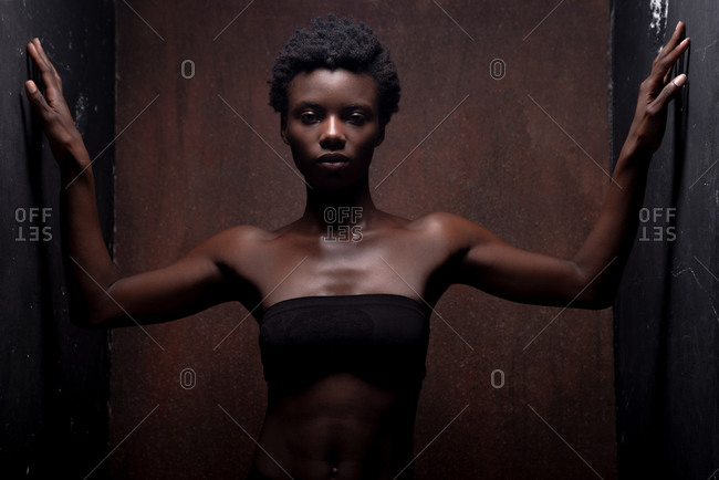 Seductive African American female model wearing black top with bare shoulders with open arms in front and looking at camera during photo session in dark studio