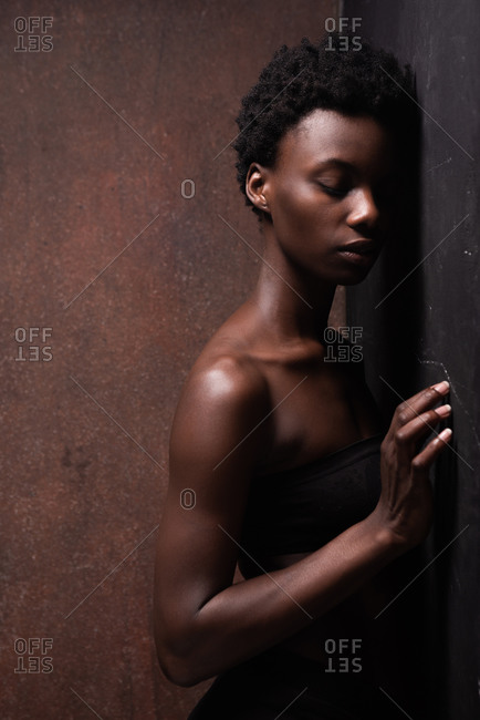 Seductive African American female model wearing black top with bare shoulders leaning against the wall and closed eyes during photo session in dark studio