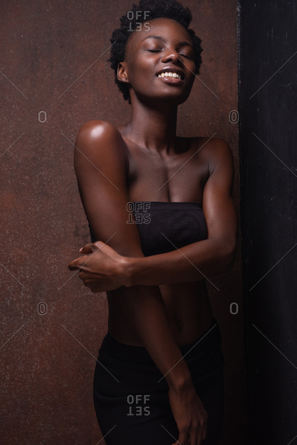 Seductive African American female model wearing black top with bare shoulders laughing and closed eyes during photo session in dark studio