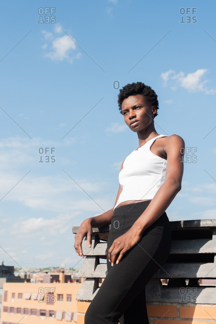 From below slim attractive African American female model standing confidently on rooftop in urban environment and looking away