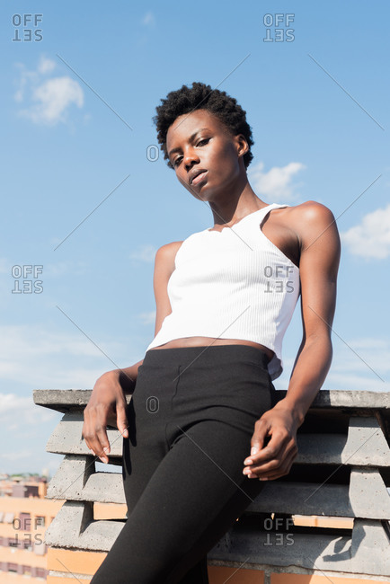 From below slim attractive African American female model standing confidently on rooftop in urban environment and looking at camera