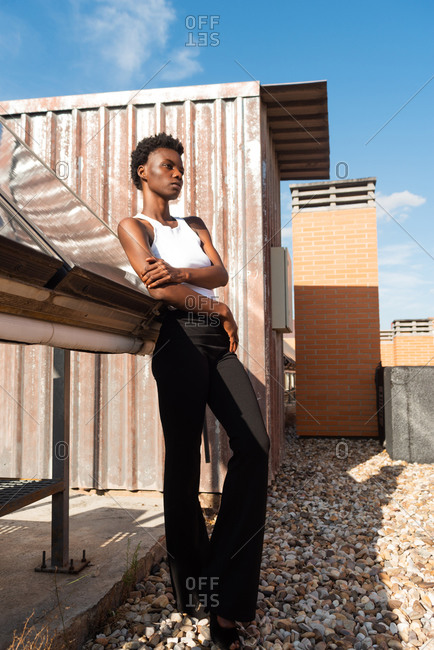 From below full body slim attractive African American female model standing confidently on rooftop in urban environment and looking away
