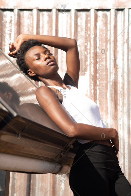 Side view graceful African American female model in white shirt laying back with eyes closed on construction on sunny roof and touching head gently