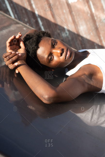 Side view graceful African American female model in white shirt laying back looking at camera on construction on sunny roof and touching head gently