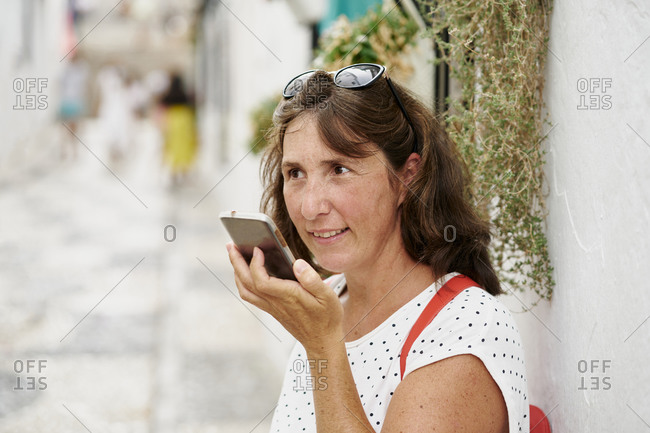 Content adult female in casual summer wear recording audio message on modern mobile phone while standing on sunny pedestrian street