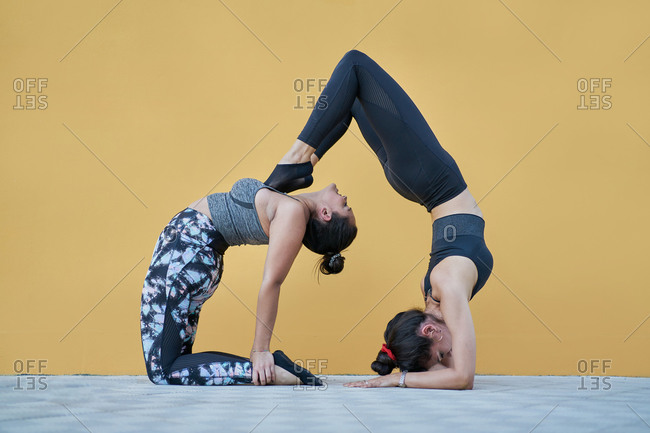 Side view full body fit females in sportswear performing gymnastic acroyoga pose against yellow wall in spacious studio