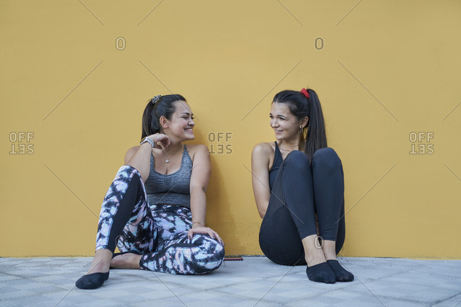 Full length cheerful young females in sportswear sitting on floor against dark yellow wall and having conversation