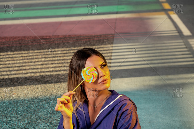 From above of young concentrated female in stylish wear covering eye with lollipop on roadway while looking away