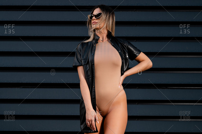 Young trendy seductive female in sunglasses standing with hand on waist while looking away near wall