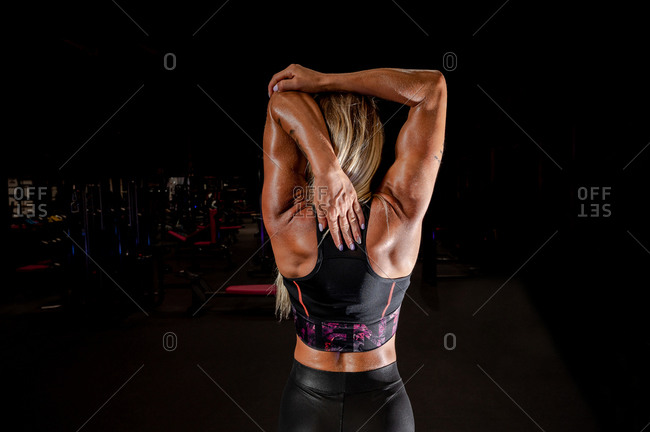 Back view of faceless muscular sportswoman in active wear warming up with raised arms in gym