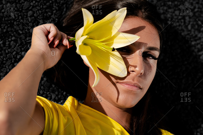From above of young glad female with closed eyes in trendy apparel covering face with colorful blooming flower on black background