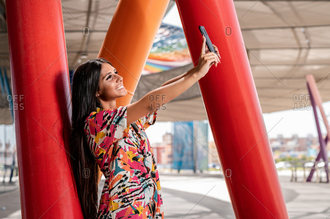Side view of young glad ethnic lady in colorful trendy apparel taking selfie on cellphone near red roofed construction