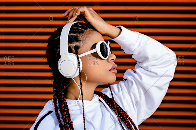 Side view of stylish African American female in casual white wear and sunglasses listening to music with headset standing against red wall with hands on face